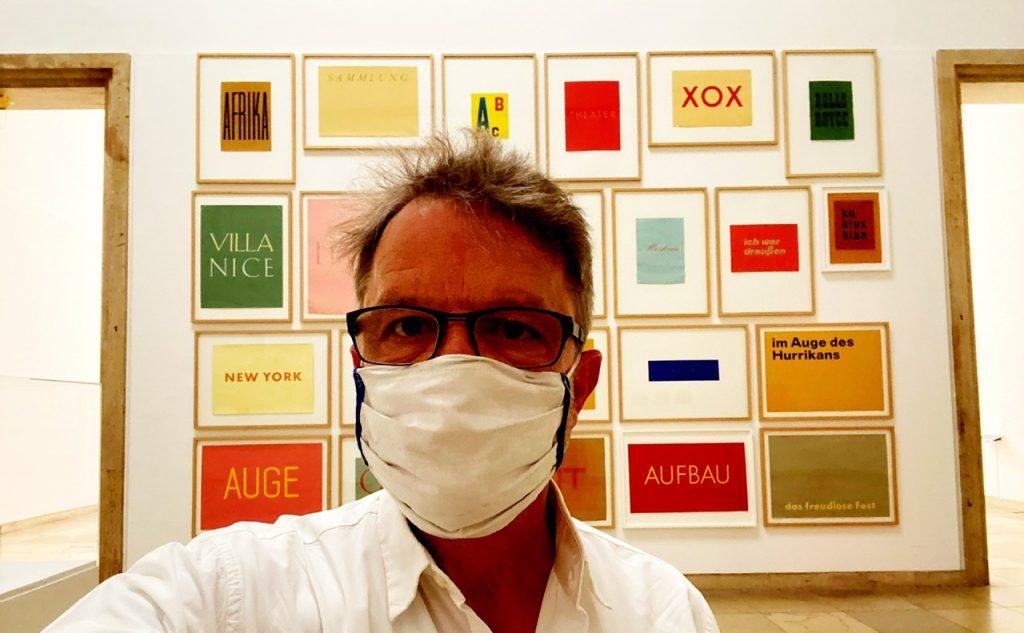 Besucher mit Gesichtsmaske im Haus der Kunst München. ImHintergrund Wortbilder