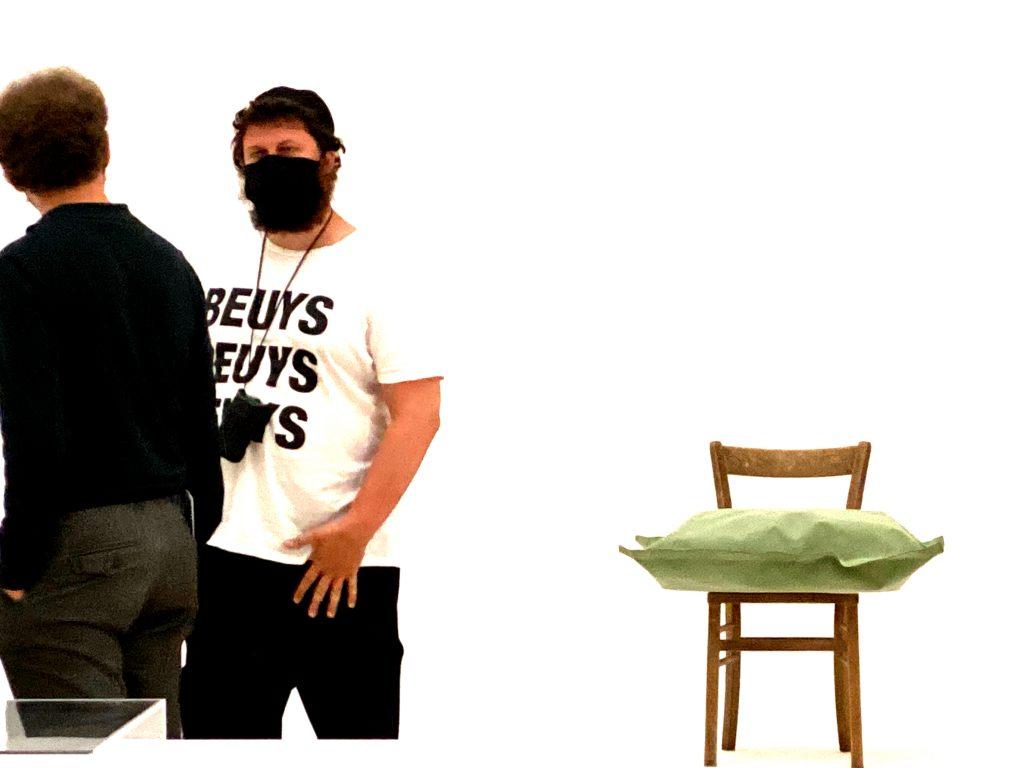 Zwei Besucher, Stuhl, Kissen, Kunstwerk